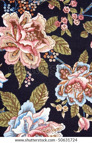 Closeup of retro tapestry fabric pattern with colorful  floral ornament on dark background.
