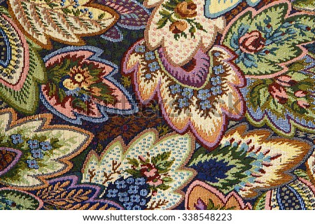 Closeup of retro tapestry fabric pattern with textured bright colorful  floral ornament.