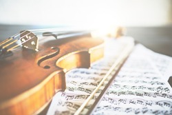 Closeup of retro violin, bow and music sheets. Concert concept