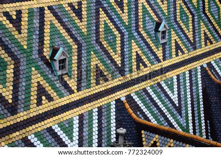 Closeup of rhombus and triangle pattern colored glazed tiles and pair of windows on steep sloping roof of medieval St. Stephen's Cathedral famous tourist spot of Vienna capital city of Austria Europe #772324009