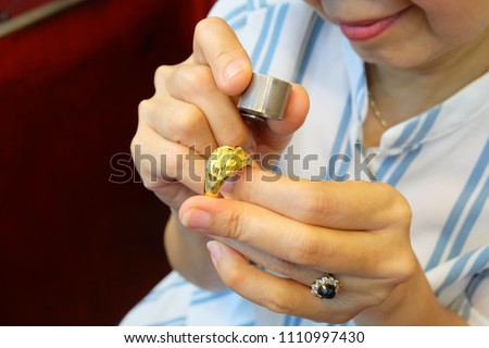 Closeup of ring through magnifying glass for evaluate or pawn at gold/pawn shop. - Shutterstock ID 1110997430