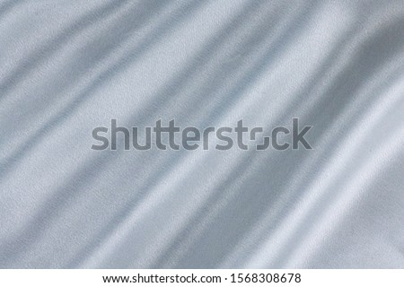 Closeup of rippled white silk fabric lines. High resolution background texture, decorative basis for design.