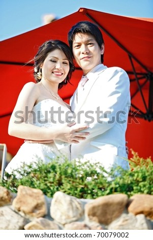closeup of romantic bride and groom with red umbrella - stock photo