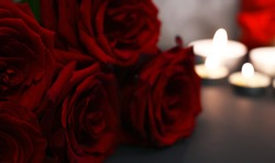 Closeup of roses.Beautiful bunch of red roses against concrete wall and candles. St.Valentine's card. Bokeh