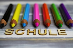 Closeup of row multi colored crayons on wood table with german word schule (english meaning: school, focus on tip of pink pencil)