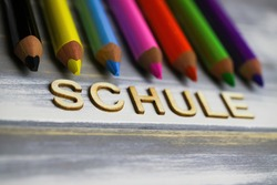 Closeup of row multi colored crayons on wood table with german word schule (english meaning: school, focus on center of letter S)