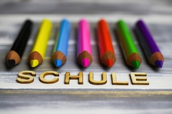 Closeup of row multi colored crayons on wood table with german word schule (english meaning: school - focus on center of letter H)