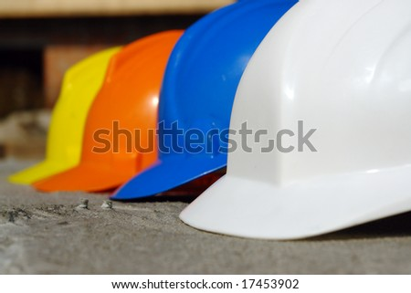 Closeup of row of four hard hats in white, blue, orange and yellow colors
