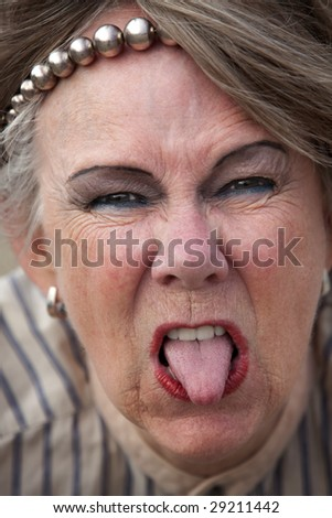 Closeup of rude old woman sticking out her tongue