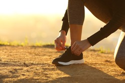 Closeup of runner woman hands tying shoelaces of shoes on the ground at sunset
