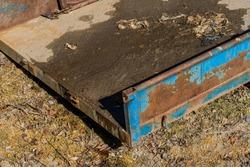 Closeup of rusty wagon tractor attachment sitting in sun.