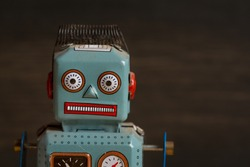 Closeup of 1950s toy tin robot on dark wood background
