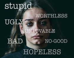 Closeup of sad, depressed schoolgirl victim of bullying on the background and insults written on the foreground isolated on black background and dramatic light. In verbal abuse and harassment.