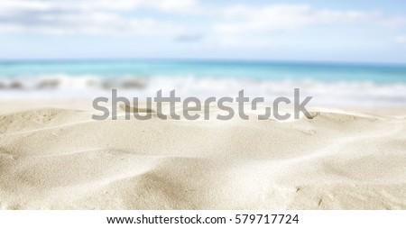 closeup of sand on beach and blue summer sky  #579717724