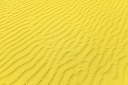 Closeup of sand pattern of a beach in the summer. Illuminating and Ultimate gray Pantone color of the year 2021