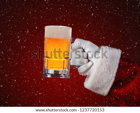 Closeup of Santa Claus holding a mug of beer. Horizontal format on a light to dark red spot background with snow effect
