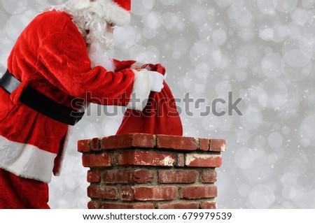 Closeup of Santa Claus placing his bag inside a chimney. Horizontal with copy space over a light bokeh background.