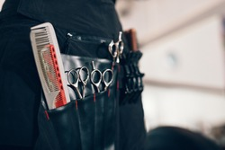 Closeup of scissors and combs in a salon holster pouch. Hairdressing tools inside a hairdresser waist pouch.