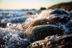 Closeup of sea waves braking on a wet seashore stone summer sunset, water splashes.