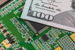 Closeup of semiconductor circuit board and 100 dollar bill. Concept of semiconductor shortage, supply and production