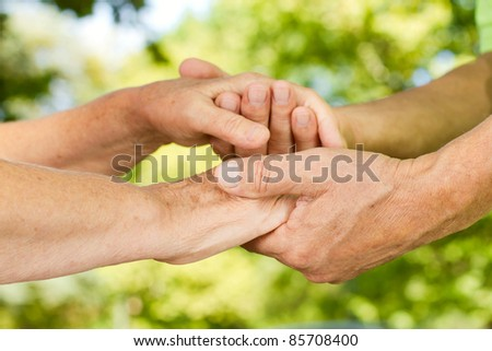 Closeup of senior couple hands holding together outdoors.