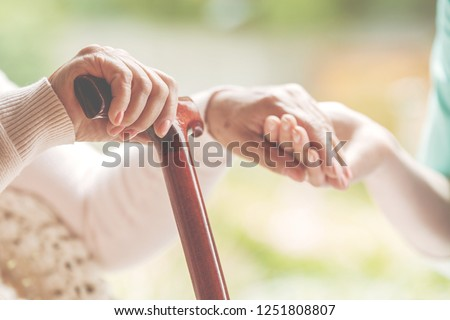 Closeup of senior lady holding walking stick in one hand and holding nurse\'s hand in the other
