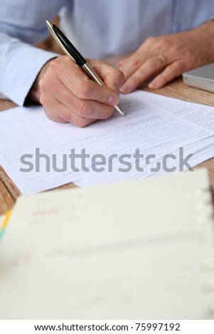 Closeup of senior man filling in tax form