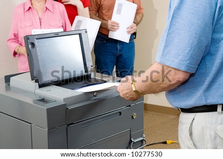 Closeup of senior man voting on an optical scanner with people waiting in line.