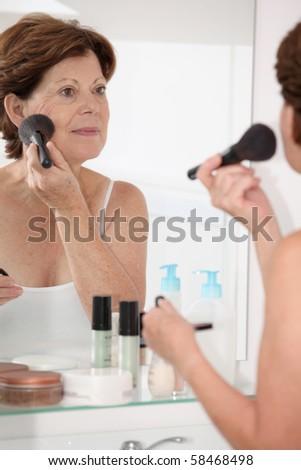 Closeup of senior woman putting makeup on