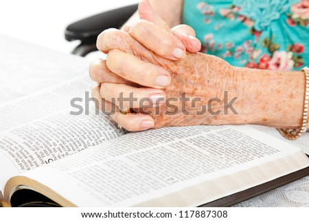 Closeup of senior woman's hands on bible, folded in prayer.