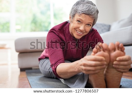 Closeup of senior woman stretching to touch toes while sitting on yoga mat. Portrait of mature woman doing her stretches at home while looking at camera. Happy healhty lady doing yoga exercises.