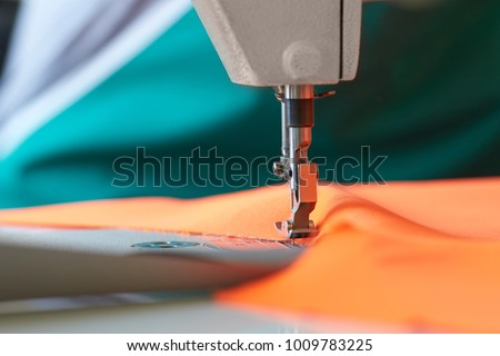 Closeup of sewing machine head and orange fabric for special protective clothing bright orange. Sewing industry.
