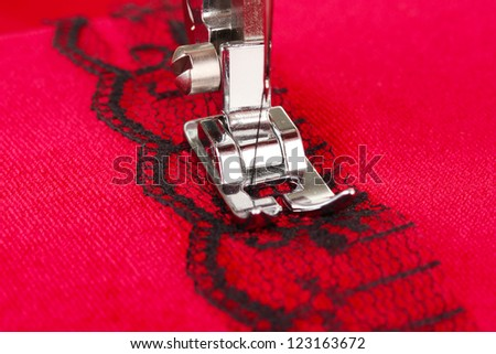 Closeup of sewing machine working part with  red cloth