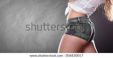 Closeup of sexy alluring woman hips and belly. Slim girl wearing white shirt and jeans shorts. Hotness and sexiness.