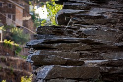 Closeup of shale slabs in the exterior with a blurry background of shale houses