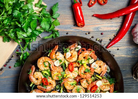 Closeup of shrimps fried on pan and fresh herbs