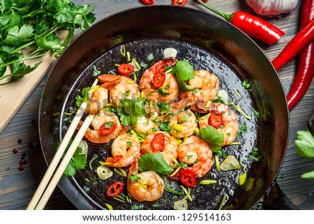 Closeup of shrimps on pan with fresh herbs