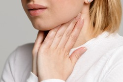 Closeup of sick young woman suffering from throat problems, holding hands on her lymph nodes, isolated. Thyroid gland, painful swallowing concept. Inflammation of the upper respiratory tract