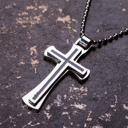 Closeup of silver Christian cross on bible