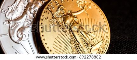 closeup of silver eagle and golden american eagle one ounce coins on black background #692278882