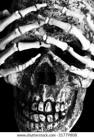 closeup of skeletal hands over eye sockets of skull