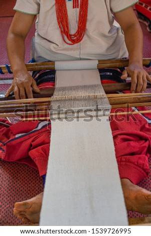 Closeup of skillful hill tribe woman's hand doing colorful cotton cloth weaving. Show traditional textile production and simply way of life by self- reliance practice. Thailand.