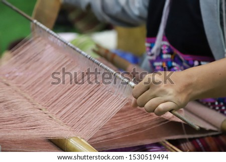 Closeup of skillful woman's hand doing colorful cotton cloth weaving. Show traditional textile production and simply way of life by self- reliance practice. Thailand.