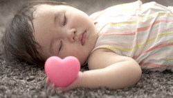 closeup of sleeping baby holding heart symbol in the living room