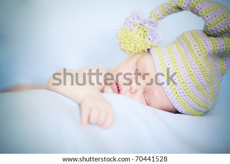 Closeup of sleeping baby in cap lying on blanket with hands in a comfortable position