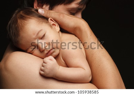 Closeup of sleeping newborn baby in the embraces of his father over black background