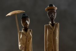Closeup of slender Cuban figurine souvenirs with a woman holding an umbrella and a man with cigar. Studio travel memorabilia low key object still life.