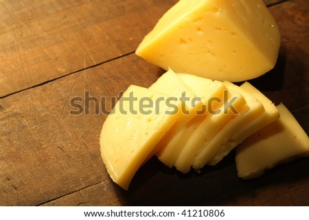 Closeup of sliced cheese lying on wooden table