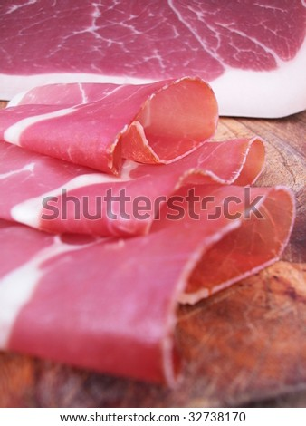 Closeup of sliced ham, typical italian prosciutto on wood trencher
