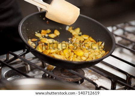 Closeup of sliced potatoes in pan on stove at commercial kitchen